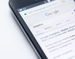 Close up of mobile phone with analytics search results on screen