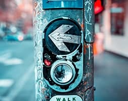 Pedestrian walk button on pole on street corner