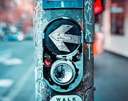 Pedestrian walk button on pole on street corner