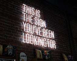 Neon sign on brick wall that says 'The sign you've been looking for