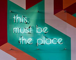 Neon sign on painted wall reading 'This must be the place'