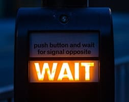 Pedestrian crossing sign lit up with the word wait