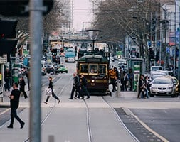 Busy Melbourne CBD street with people, cars and trams