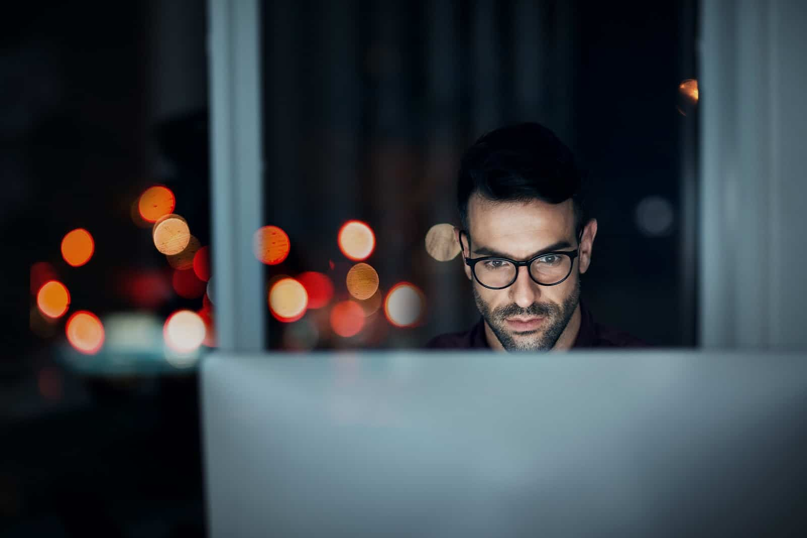 Man sitting at his office desk at night with computer screen in front of him