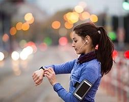 Female runner setting timer on watch
