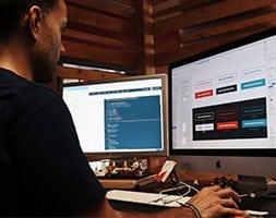 Man at computer desk developing a website