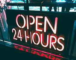 Red neon sign in front of a shop window which reads Open 24 Hours