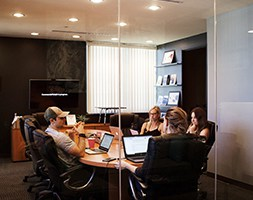 Group of people in an office meeting sitting around a boardroom table with laptops