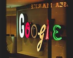 Neon Google sign o a wall seen through an office window